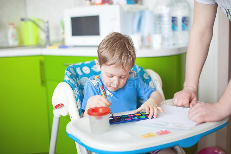 Glückliche freundliche Kindzeichnung mit Pinsel im Album unter Verwendung vieler Anstrichhilfsmittel Hand, die lego Wand aufbaut lizenzfreie stockfotos