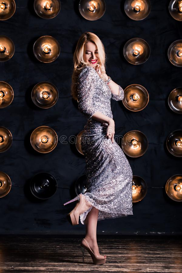 Glückliche frohe blonde Frau in einem langen silbernen Kleid auf einem schwarzen Hintergrund Feier, Partei, neues Jahr, Geburtsta stockbilder