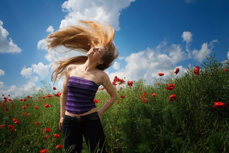 Glückliche frohe Frau auf dem schönen Mohnblumegebiet stockfoto