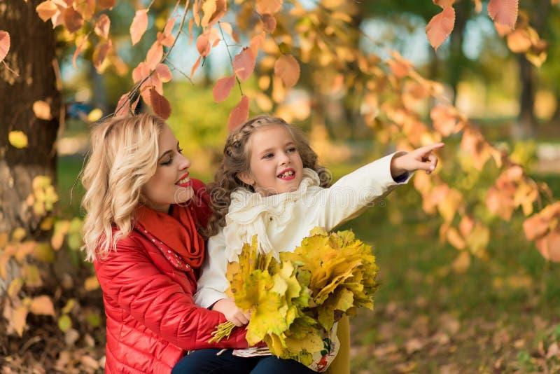 Glückliche frohe Frau, die Spaß mit ihrem Mädchen in der Herbstfarbe hat lizenzfreies stockbild