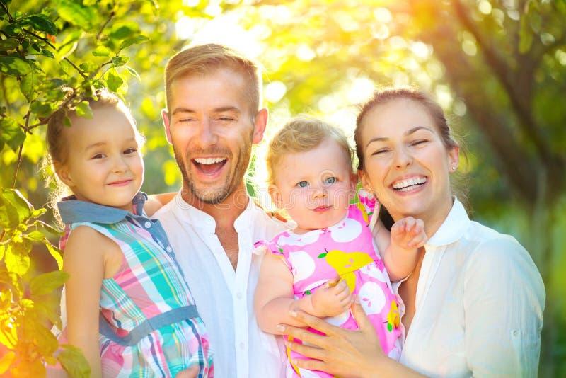 Glückliche frohe junge Familie mit Kleinkindern draußen stockfoto