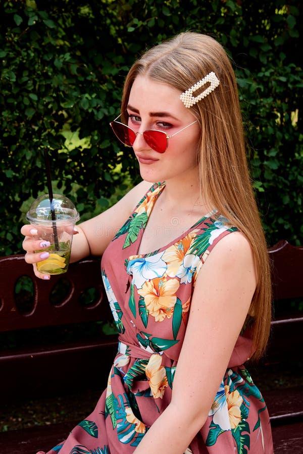 Glückliche frohe junge Frau mit farbigem Zuckerwatte-Getränk frischem mojito Cocktail lizenzfreies stockbild