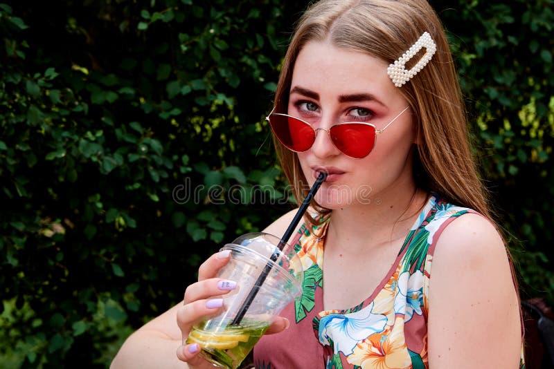 Glückliche frohe junge Frau mit farbigem Zuckerwatte-Getränk frischem mojito Cocktail stockfotografie
