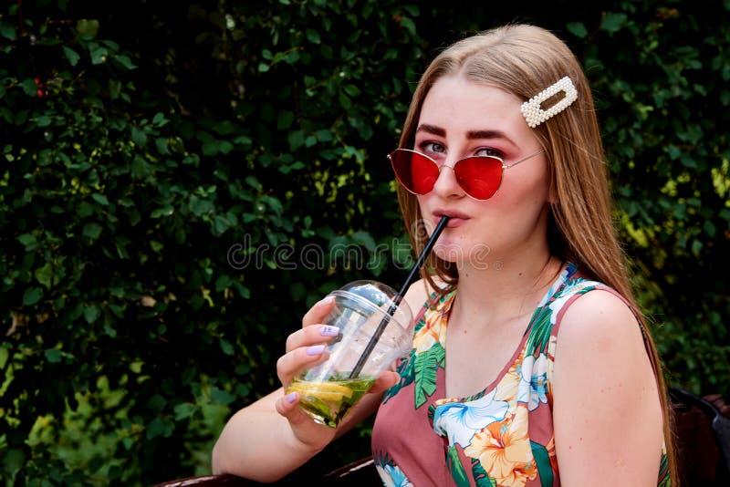Glückliche frohe junge Frau mit farbigem Zuckerwatte-Getränk frischem mojito Cocktail stockfotos