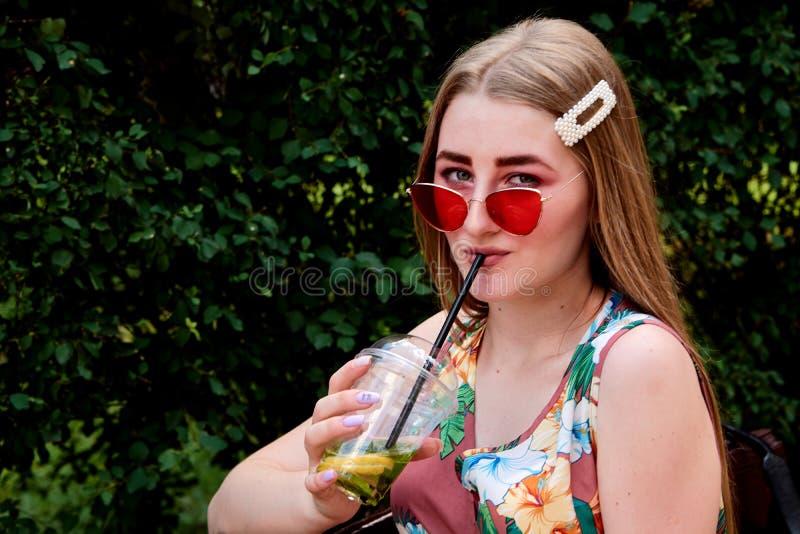 Glückliche frohe junge Frau mit farbigem Zuckerwatte-Getränk frischem mojito Cocktail lizenzfreie stockfotografie