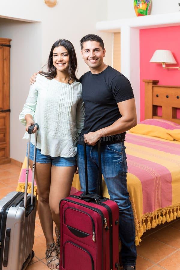 Glückliche Gäste mit Koffern im bunten Raum des Flitterwochen-Erholungsortes lizenzfreie stockfotos