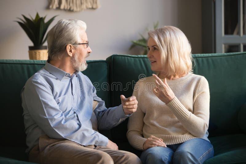 Glückliche gealterte Familie, reife Frau und Ehemann, die zu Hause spricht lizenzfreie stockfotos