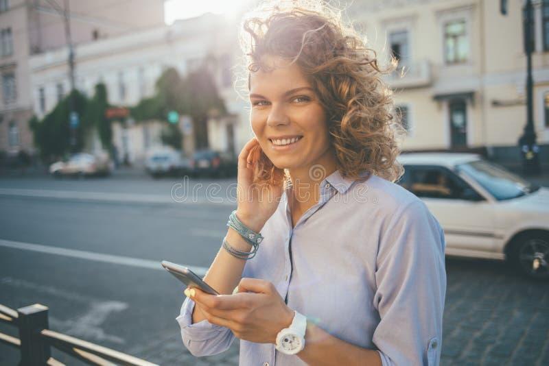 Glückliche gelockte junge Frau, die blaues Hemd trägt stockbilder