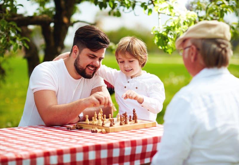 Glückliche Generation der dreiköpfigen Familie von den Männern, die im Frühjahr Garten des Schachs spielen stockfotografie