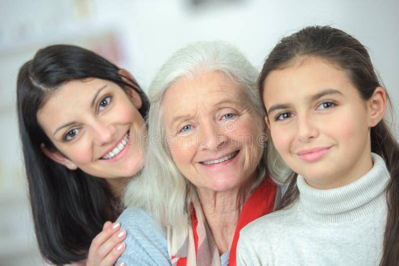 Glückliche Generationen der Familie drei, die Kamera lächeln und betrachten lizenzfreies stockfoto