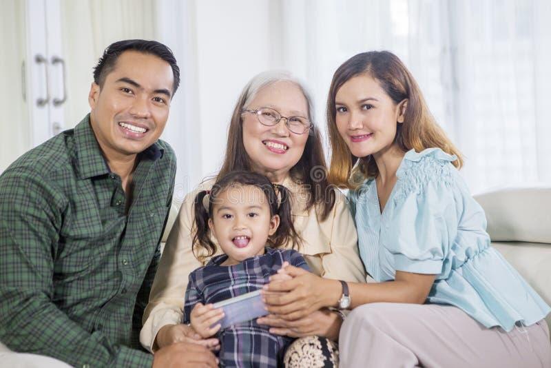 Glückliche Generationsfamilie benutzt ein Telefon zu Hause lizenzfreie stockfotos