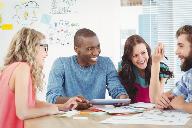 Glückliche Geschäftsfachleute, die digitale Tablette am Schreibtisch verwenden lizenzfreies stockfoto