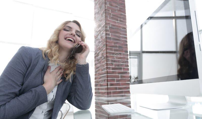 Glückliche Geschäftsfrau auf ihrem Arbeitsplatz stockbild