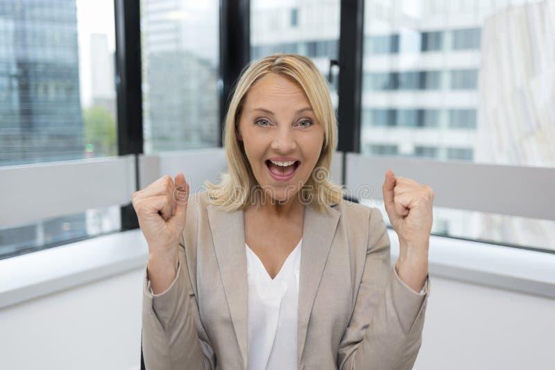 Glückliche Geschäftsfrau bewaffnet oben Moderner Bürohintergrund stockfotos
