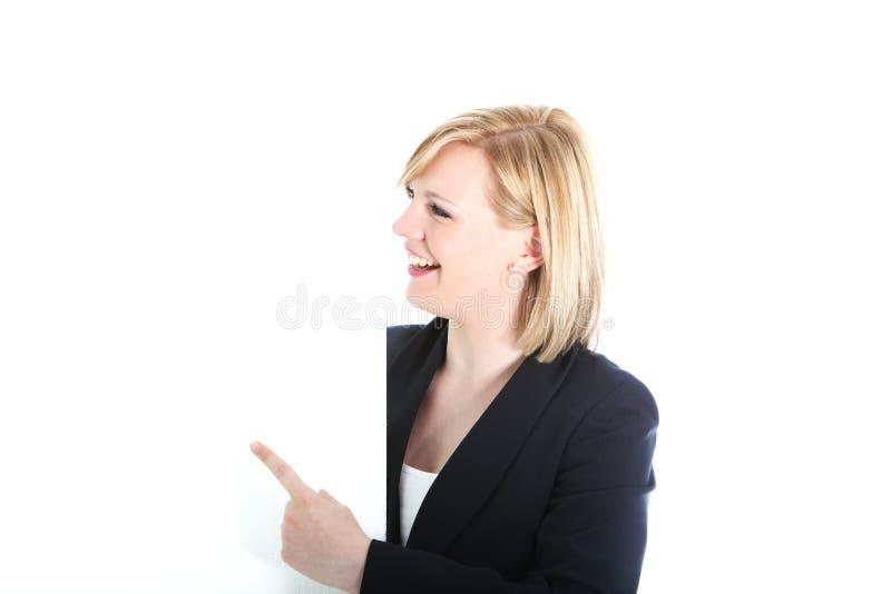Glückliche Geschäftsfrau, die auf weißen Vorstand zeigt lizenzfreies stockfoto