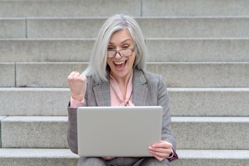 Glückliche Geschäftsfrau, die an den guten Nachrichten zujubelt lizenzfreie stockbilder