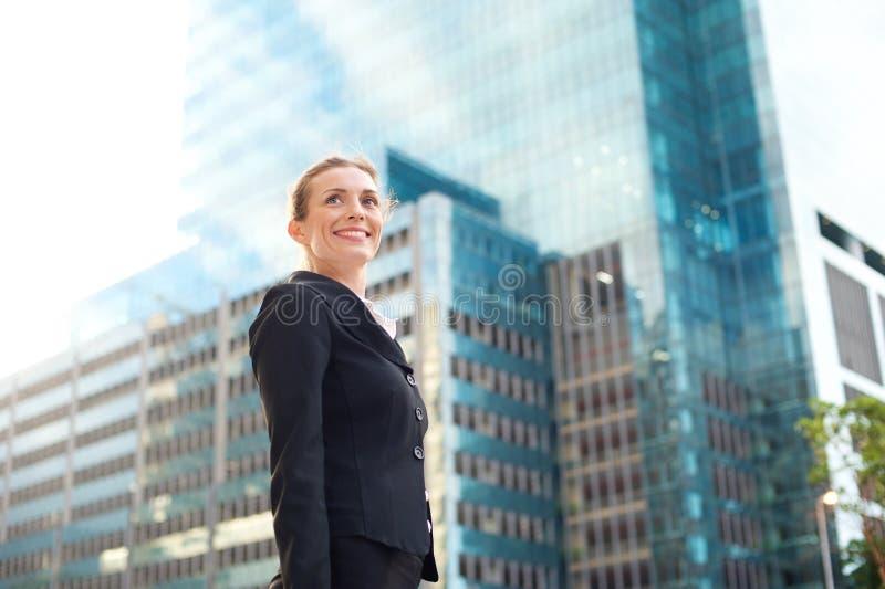 Glückliche Geschäftsfrau, die draußen in die Stadt geht stockbild