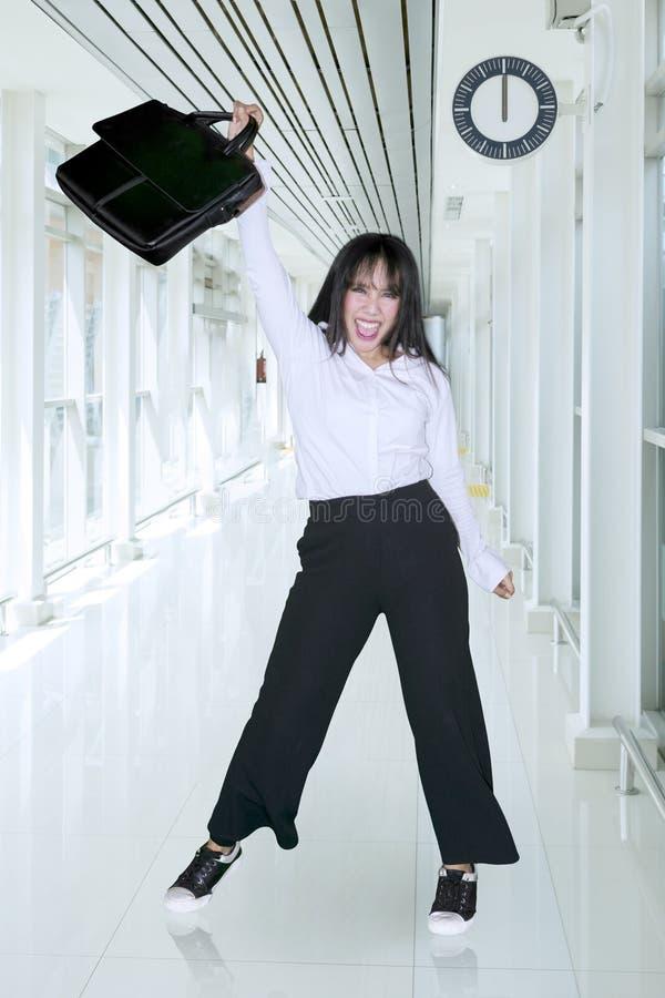 Glückliche Geschäftsfrau, die einen Koffer im Korridor anhebt stockfotos