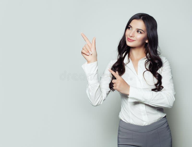 Glückliche Geschäftsfrau, die ihren Finger auf leeren Kopienraum zeigt stockfotos