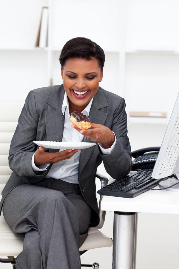 Glückliche Geschäftsfrau, die im Büro isst stockfotografie