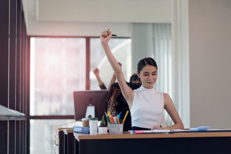 Glückliche Geschäftsfrau, die im Büro mit Ihren Händen oben arbeitet lizenzfreie stockfotos