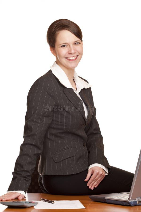 Glückliche Geschäftsfrau, die im Büro am Schreibtisch sitzt lizenzfreies stockbild