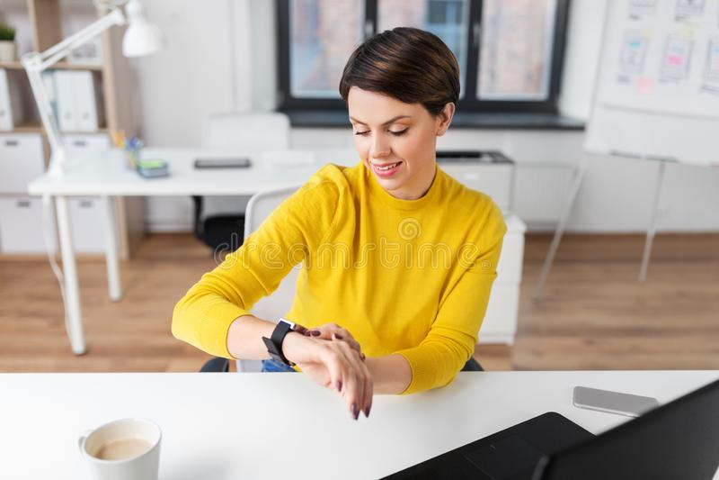 Glückliche Geschäftsfrau, die intelligente Uhr im Büro verwendet lizenzfreie stockfotografie