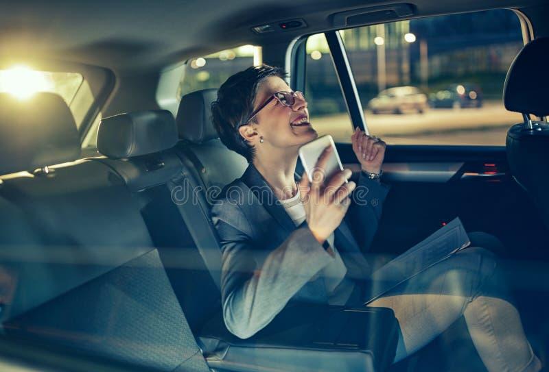 Glückliche Geschäftsfrau, die mit Auto bis zum Nacht auf Geschäftsreise reist stockfoto