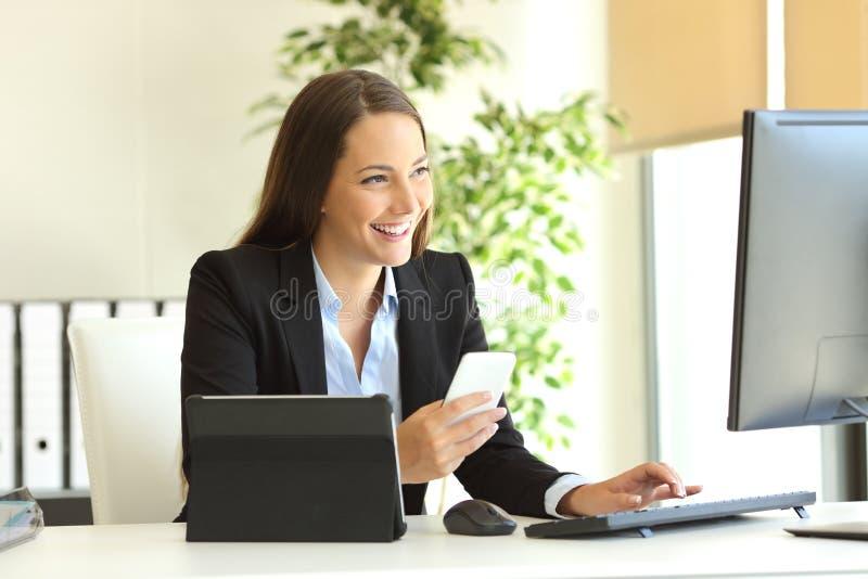 Glückliche Geschäftsfrau, die mit mehrfachen Geräten arbeitet lizenzfreies stockfoto