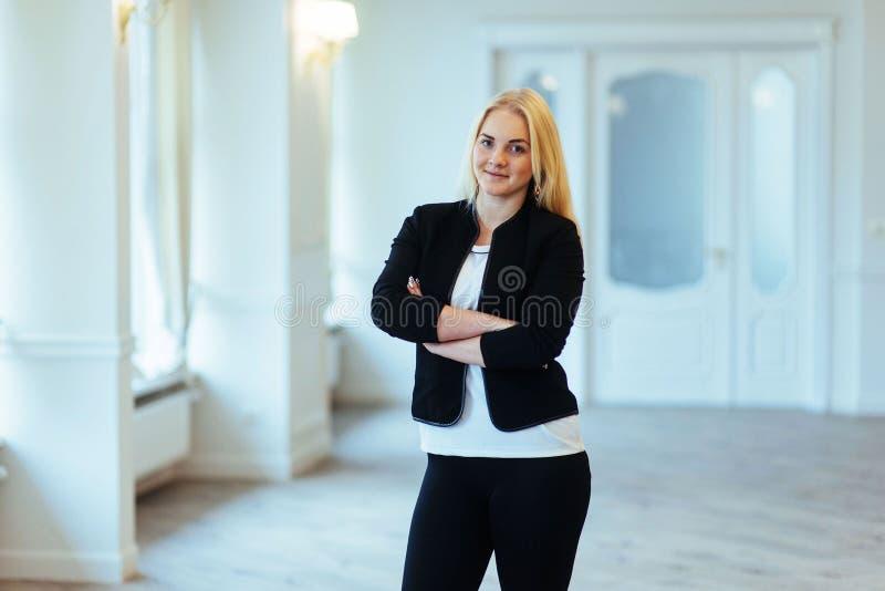 Glückliche Geschäftsfrau, die mit modernem Gebäude als b überzeugt schaut stockbild