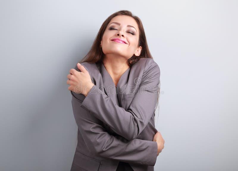 Glückliche Geschäftsfrau, die mit natürlichem emotionalem enjo sich umarmt stockfoto