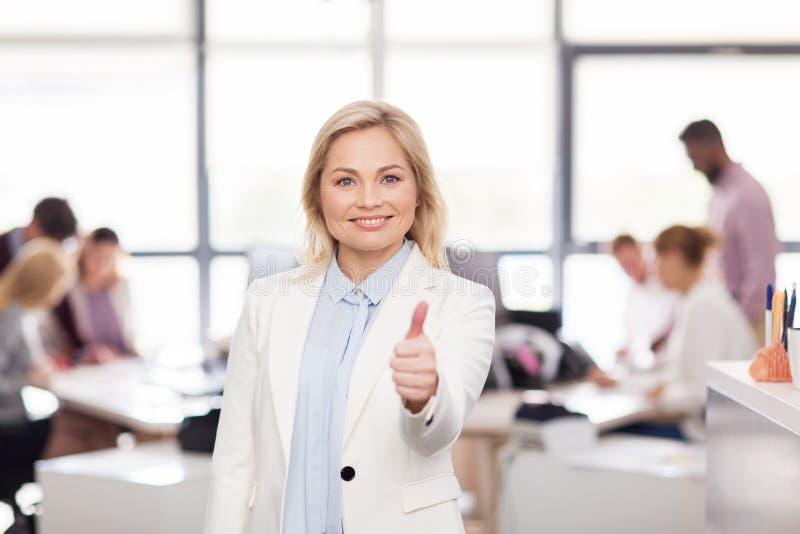Glückliche Geschäftsfrau, die sich Daumen im Büro zeigt lizenzfreie stockfotografie