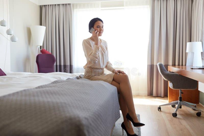 Glückliche Geschäftsfrau, die um Smartphone im Hotel ersucht stockbilder