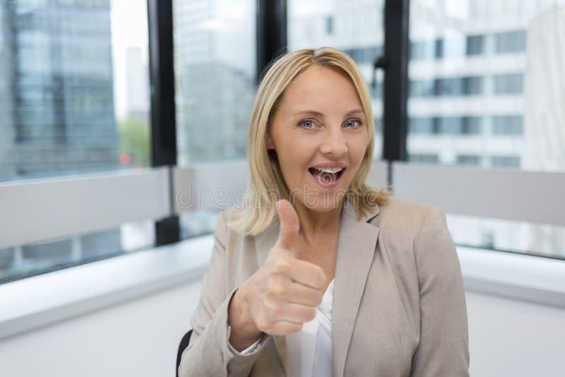 Glückliche Geschäftsfrau greift oben ab Moderner Bürohintergrund lizenzfreie stockfotografie