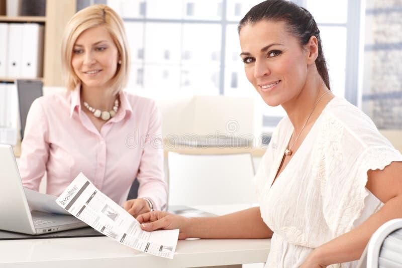 Glückliche Geschäftsfrau im Büro mit Geschäftsbericht stockfotos