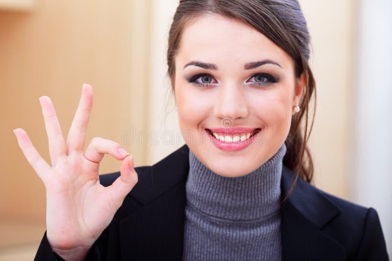 Glückliche Geschäftsfrau im Büro zeigt okayzeichen stockfoto