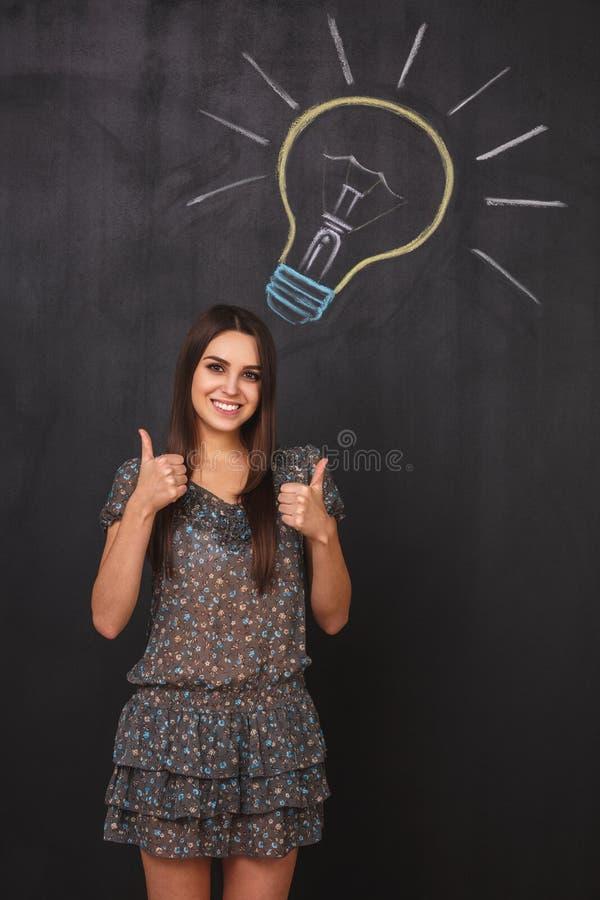Glückliche Geschäftsfrau im Kleid zeigt sich Daumen nahe einer Glühlampe auf einer Tafel lizenzfreie stockbilder