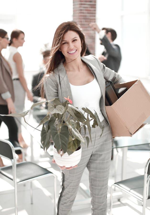 Glückliche Geschäftsfrau mit den persönlichen Sachen, die im neuen Büro stehen stockfotografie
