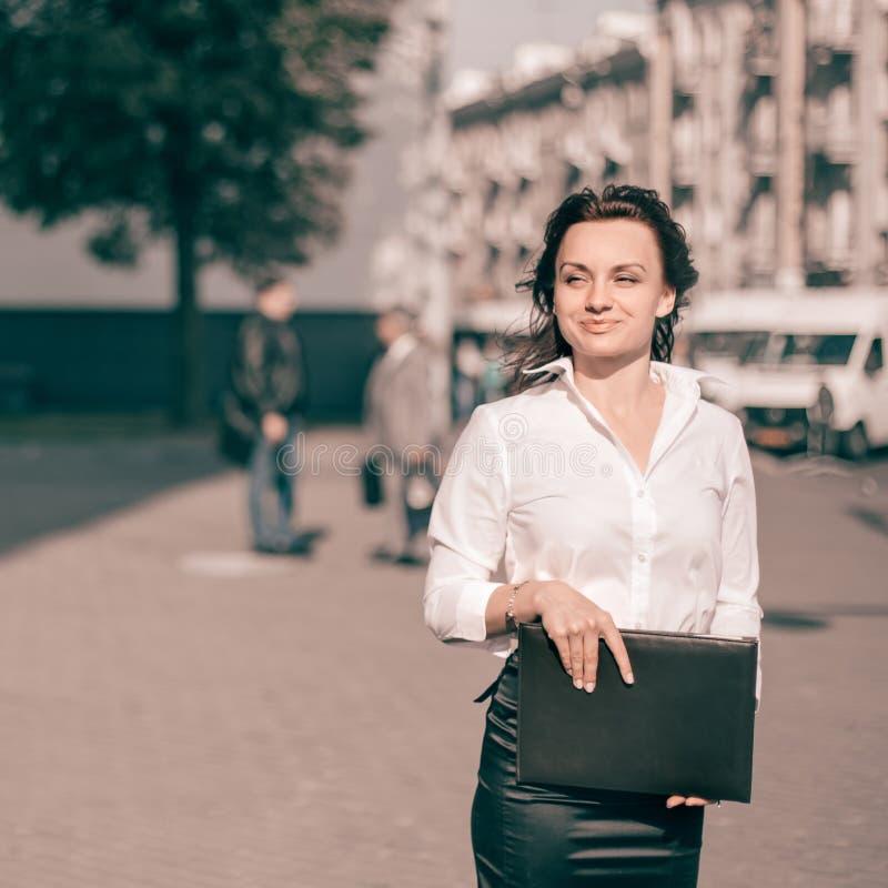 Glückliche Geschäftsfrau mit Klemmbrettstellung auf Stadtstraße stockfotografie