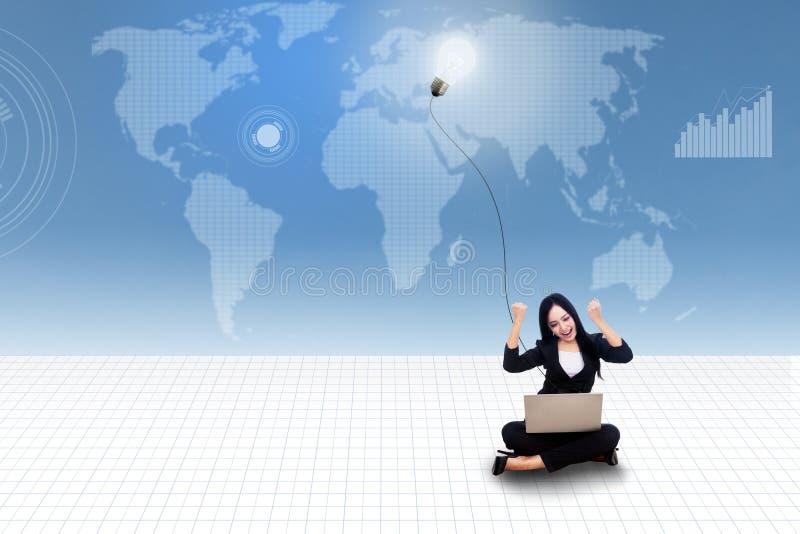 Glückliche Geschäftsfrau mit Laptop und Glühlampe auf blauer Weltkarte stockfotografie