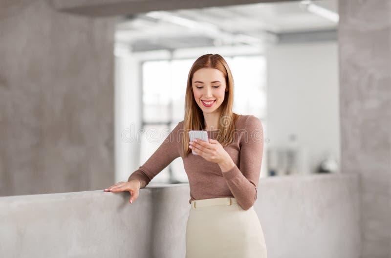 Glückliche Geschäftsfrau mit Smartphone im Büro lizenzfreies stockbild