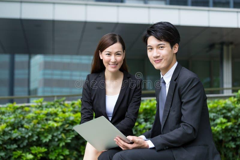 Glückliche Geschäftsfrau und Mann halten mit Laptop-Computer stockfotos