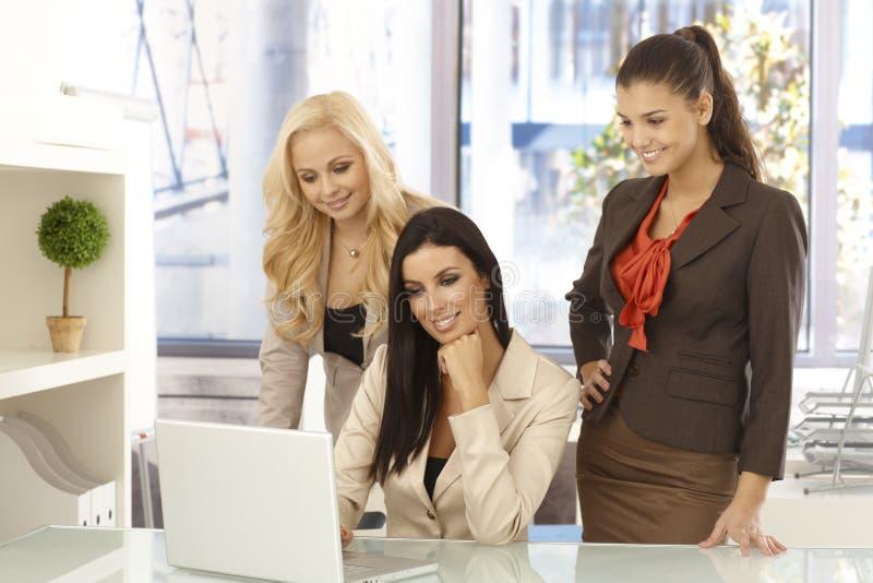 Glückliche Büroangestellte, die an Computer im Büro arbeiten stockbild