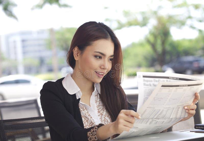 Glückliche Geschäftsfraulesezeitung und -lächeln stockbild