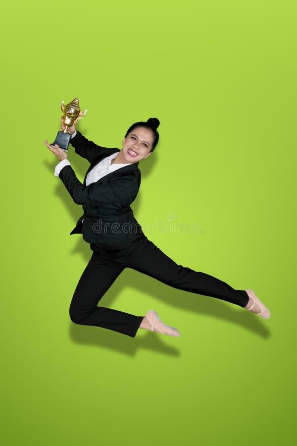 Glückliche Geschäftsfrautänze mit Trophäe auf Studio lizenzfreie stockfotos