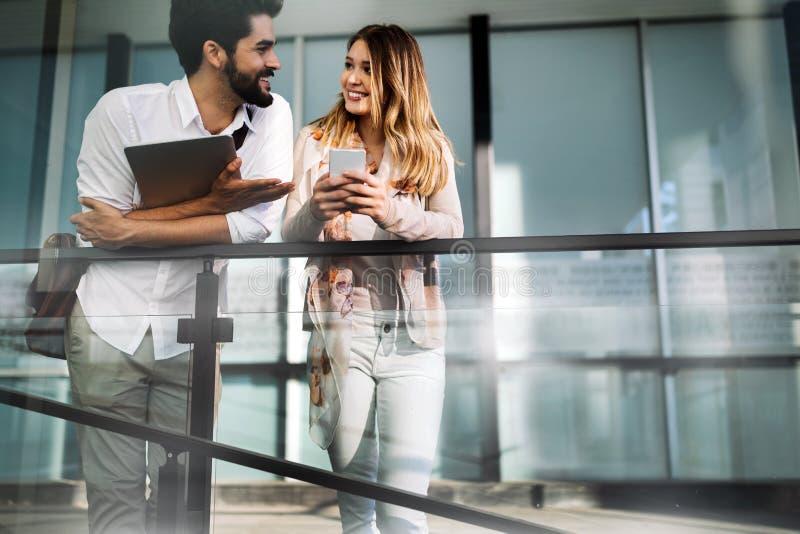 Glückliche Geschäftskollegen, die in einem Bruch lächeln und sprechen stockfotografie