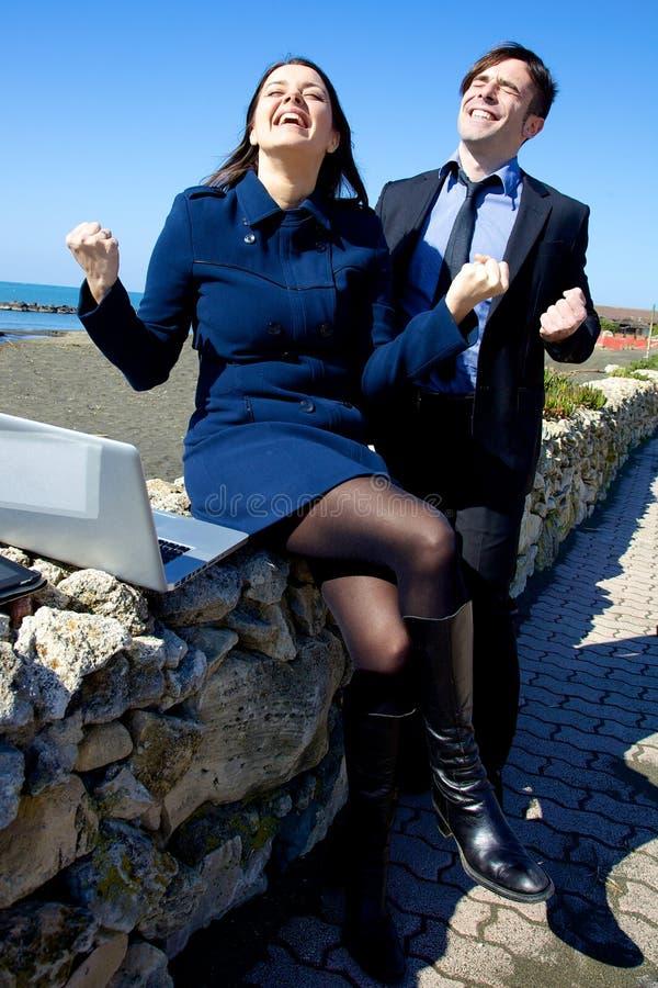 Glückliche Geschäftsleute, die an dem Strand arbeiten stockfoto