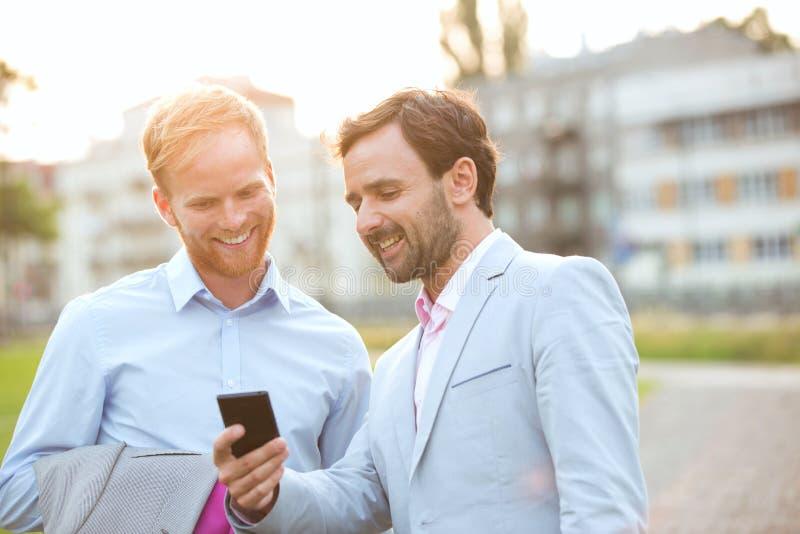 Glückliche Geschäftsmänner unter Verwendung des Handys in der Stadt stockbild