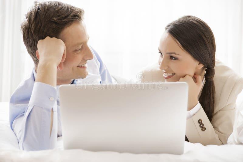 Glückliche Geschäftspaare mit dem Laptop, der einander im Hotel betrachtet lizenzfreies stockfoto