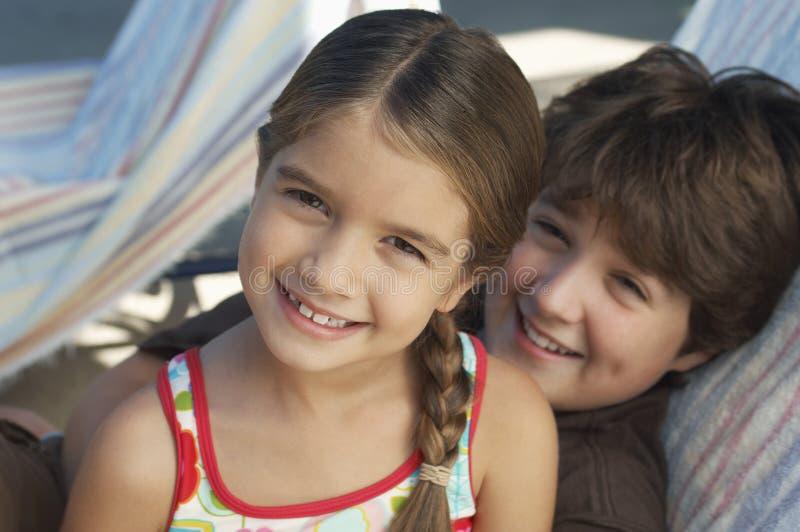 Glückliche Geschwister, die auf Deckchair sich entspannen stockbild